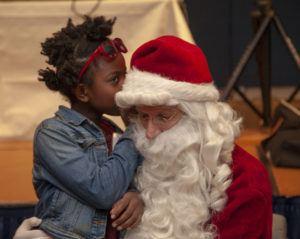 Little girl whispering into Santa's ear